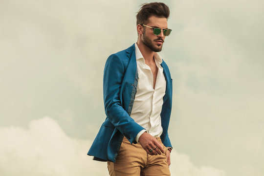 smart casual man with sunglasses on grey clouds background