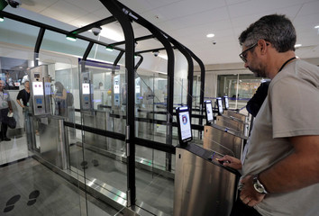 A passenger places his passport on a scanner before entering an airlock for facial recognition at Nice international airport's immigration section