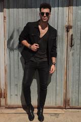 handsome man in black clothes standing outside near garage door