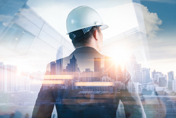 The double exposure image of the engineer standing back during sunrise overlay with cityscape image. The concept of engineering, construction, city life and future. Wall mural