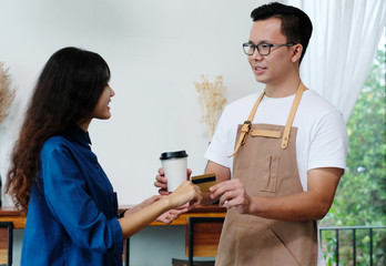 Customer paying coffee by credit card at cafe counter, food and drink business concept