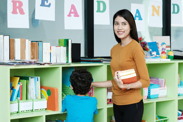 Young asian woman holding books standing with boy at library background, education concept