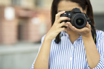 Girl holding the camera outdoors with copy space