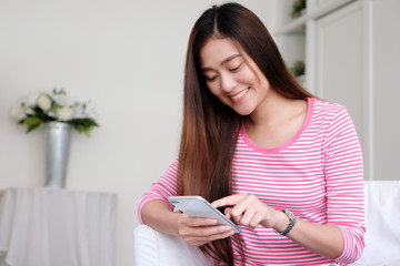 Young asian woman using smart phone with smiling, happy and relax emotion in white room background, people on phone, lifestyle
