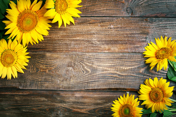 Wall Mural - Beautiful sunflowers on a wooden table. View from above. Background with copy space.