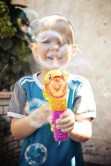 boy doing soap bubbles in the garden