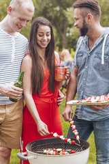 Smiling woman and friends grilling shashliks during garden party in the summer