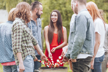 Happy woman grilling shashlik with friends during birthday party in the garden