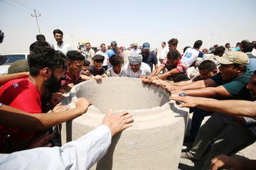 Iraqi protesters push concrete blocks to block the road during a protest in south of Basra