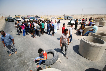 Iraqi protesters block the road during a protest in south of Basra