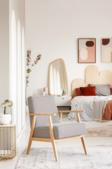Patterned wooden armchair in pastel bedroom interior with poster and mirror near bed. Real photo