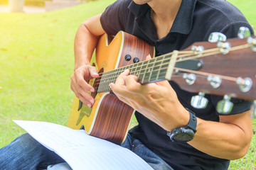 Musician playing guitar in the park