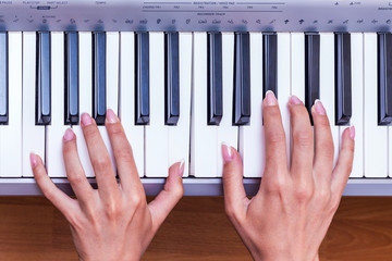 The girl plays the piano. Hands of a woman with exquisite manicure on the piano keys, top view_