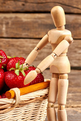 Wooden dummy with fresh ripe strawberries. Healthy ripe strawberries in basket and wooden figurine, vertical image. Gardening of strawberry.