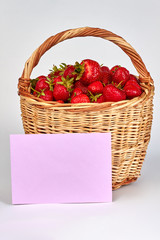 Fresh strawberries in wicker basket. Ripe delicious strawberries and blank paper card. Organic food concept.