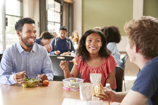 Teacher And Students Eating Lunch In High School Cafeteria During Recess