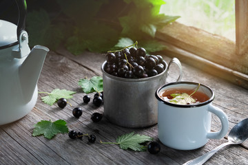Mug of black currants, enameled cup of fruit tea with black currant berries, tea kettle on wooden table in a retro village house.