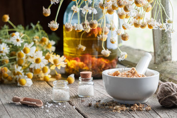 Mortar of dried healing herbs, homeopathic globules, bottle of oil or infusion and bunches of dry chamomile plant. Homeopathy and herbal medicine.