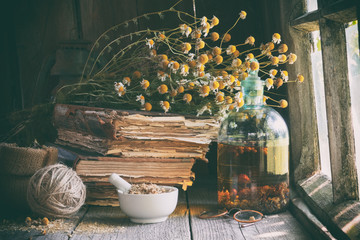 Poster Retro Mortar of dried healing herbs, bottle of essential oil or infusion, old books and bunch of dry chamomile plant. Herbal medicine.