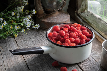Bowl full of raspberries on wooden table in a retro village house.