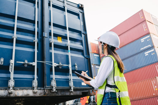 woman staff checking container box for logistic export and import