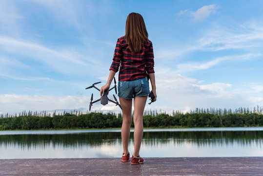 Young woman is standing and holding drone. Aerial video and photography maker.