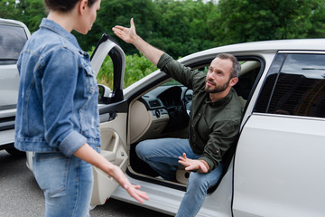 male and female drivers quarreling on road after car accident