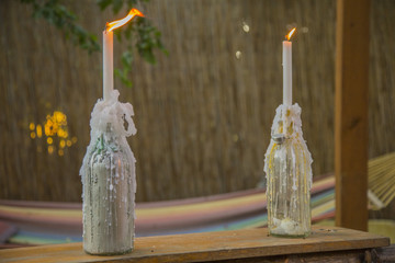 image of two bottles completely covered by candles wax with two burning candles