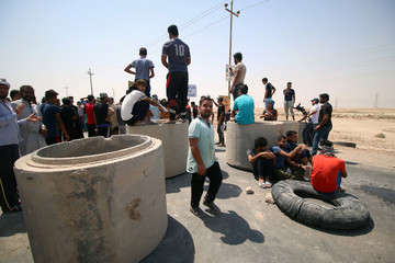 Iraqi protesters gather to block the road during a protest in south of Basra