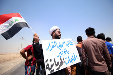 "A protester holds a sign that reads ""We ask the decision makers to provide the things we are deprived of"" during a protest in south of Basra"