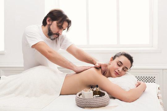 Male masseur doing professional body massage