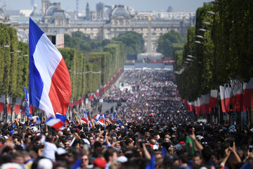 Supporters wave French national flags while they gather on the Champs-Elysees avenue in Paris