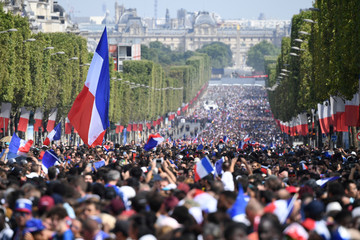 Supporters wave French national flags while they gather on the Champs-Elysees in Paris