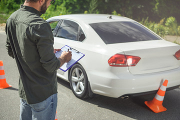 cropped image of man writing something to car insurance on road