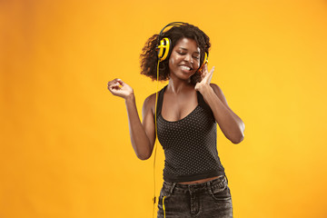 Studio portrait of adorable curly girl happy smiling during photoshoot. Stunning african woman with light-brown skin relaxing in headphones