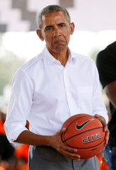 Former U.S. President Barack Obama holds the ball at the basketball court during the launch of Sauti Kuu resource centre near his ancestral home in Nyangoma Kogelo village in Siaya county