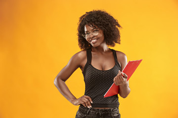 portrait of a beautiful friendly African American woman with a curly afro hairstyle and red folder