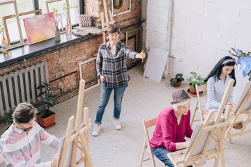 Full length portrait of elegant smiling female teacher watching group of students painting at easels in art class, copy space