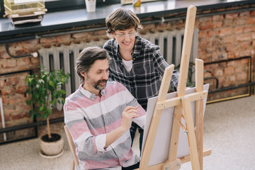 High angle portrait of mature man painting sitting by easel in art studio with female art teacher watching him in art class, copy space