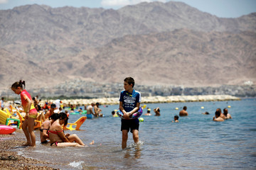 Visitors bathe in the Red Sea at a beach in Eilat