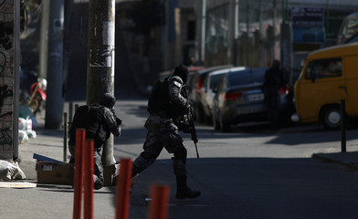 Police take position during an operation against drug gangs in Alemao slums complex in Rio de Janeiro