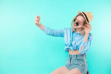 side view portrait of stylish beautiful girl taking a selfie. copy space.
