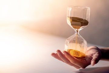 Close up of gold sand running through the shape of modern hourglass on male hand.Time passing and running out of time. Urgency countdown timer for business deadline concept with copy space