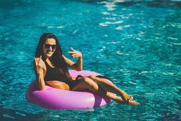 pretty happy brunette woman in black bikini sitting on the rubber ring in the swimming pool. Summer Vacation. Enjoying suntan. Weekend on resort