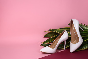 White women's leather shoes lie on a plant on a pink background