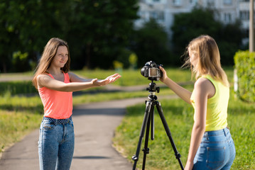Two girls are students. Summer in nature. Conduct a conversation. Record vlog and blog. Record video lesson for Internet. Use camera with tripod.
