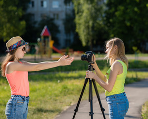 Two girls girlfriend. Summer in nature. Writes video to the camera. Record vlog and blog. Record video lesson for Internet. Use camera with tripod.