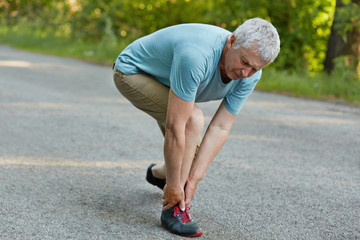 Active healthy mature sportsman stands sideways, feels pain in leg after long jogging, wears sneakers and casual clothes, stands on road, pulled muscle. Pensioners and physical activity concept