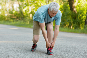 Outdoor view of sporty healthy male pensioner stretches leg, pulled muscle, dressed in sportswear and sneakers, stands on asphalt, can`t run anymore, enjoys sunny day and fresh air. Sport concept