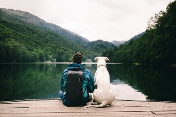 Man sitting with a dog on dock at the lake